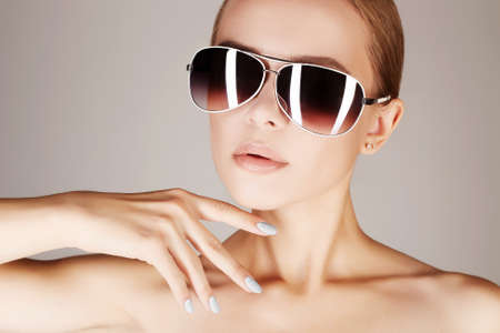 beautiful young woman in sunglasses.fashionable girl with solarium lamp reflection in her eyeglasses