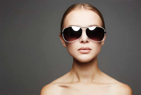 beautiful young woman in sunglasses.fashionable girl with lamp reflection in her eyeglasses