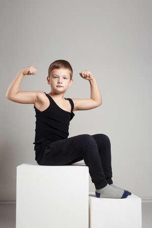 어린이. 재미 있은 어린 소년. 양손에 그의 손 알 통 근육을 보여주는 스포츠 아이 .funny 자식 스톡 콘텐츠