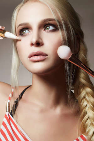 Beautiful woman face. Make-up artist applies cosmetics. model blonde girl Banco de Imagens