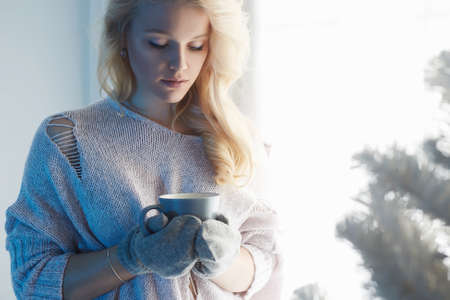 winter home lifestyle girl with hot coffee. beautiful young blond woman stay near the window and christmas tree
