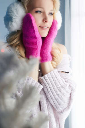 happy girl in pink mittens and fur hat. beautiful young blond woman. Christmas mood. winter lifestyle