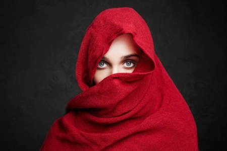 beautiful woman covers her face with a red cloth hi-jab. fashion muslim style girl. make up Stock Photo