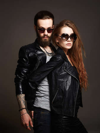 fashion beautiful couple in sunglasses and leather.bearded man and beauty girl Фото со стока
