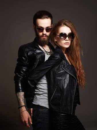 mode mooi paar in zonnebril en leer. bebaarde man en schoonheid meisje