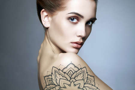 Young blond woman with tattoo.Beautiful blonde Girl with make-up.fashion portrait Imagens