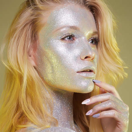 Portrait of Beautiful Woman with Sparkles on her Face. Girl with Art Make-Up in Color Light. Fashion blonde Model with Colorful Makeup