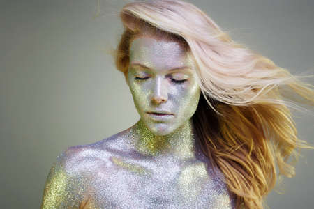 Portrait of Beautiful Woman with Sparkles on her Face and body. Girl with Art Make-Up in Color Light. Fashion flying Blond hair Model with Colorful Makeup