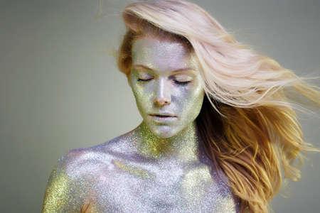 Portret van mooie vrouw met glitters op haar gezicht en lichaam. Meisje met kunst make-up in kleur licht. Manier die Blond haarmodel met Kleurrijke Make-up vliegt