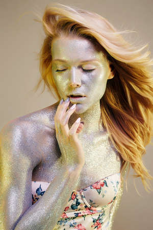 Portrait of Beautiful Woman with Sparkles on her Face and Body. Girl with Art Make-Up in Color Light