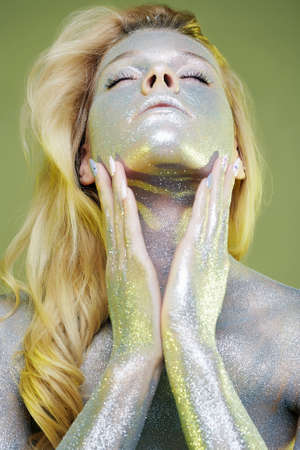 Portrait of Beautiful Girl with Sparkles on her Face and Body. Young Woman with Art Make-Up in green Light