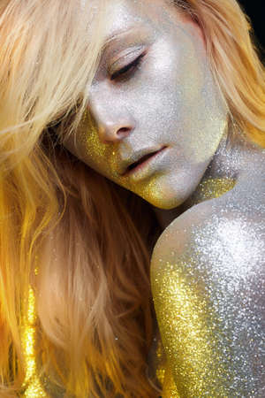 Beautiful Woman with Sparkles. Golden Girl with Art Make-Up in Color Light. Fashion blonde Model with Colorful Makeup and hair Stock Photo