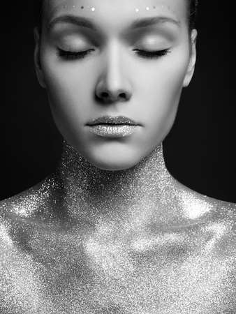 Portrait of Beautiful young Woman in Sparkles. Girl with Art Make-up