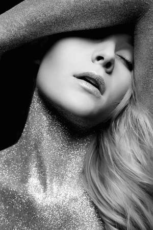 Silver Girl. Beautiful Woman with Sparkles on her Face and Body. Black and white Fashion Portrait