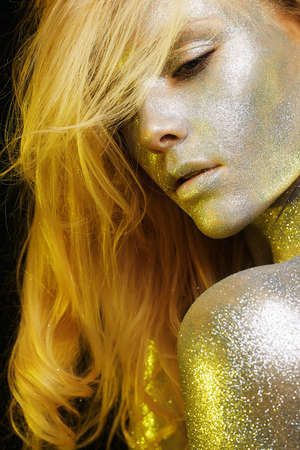 Beautiful Woman with Sparkles on Face and body. Girl with Art Make-Up in Color Light. Fashion blonde Model with Colorful Makeup Stock Photo