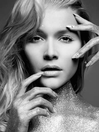 Silver Girl. Black and White beauty Portrait of Beautiful young Woman with Sparkles. Girl with Art Make-Up and Hairstyle