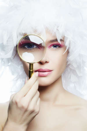 the Girls eye in a zoom. Eye through a magnifying glass. Young Sexy Woman in feather Hat, closeup. Beauty Make-up