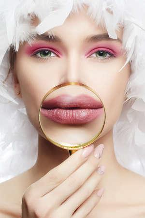 ズームで女の子の唇。虫眼鏡を通して顔。大きな唇を持つ醜い若い女性。羽帽子、クローズアップ。美容メイク、リップオーグメンテーション