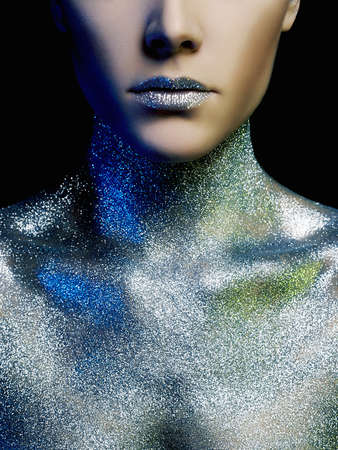 Portrait of Beautiful young Woman in Sparkles. Beauty Girl with Art Make-Up in Color Light