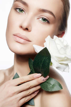Beautiful Nude Make-up Woman with Flower. Beauty Portrait of girl with White Rose Flower. Clean Face, care Stock Photo