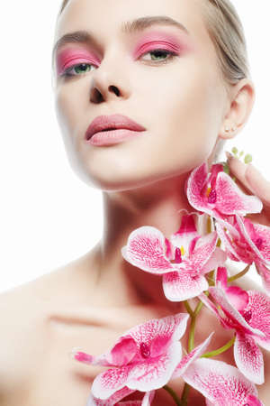 Beautiful young Woman with Make-up and Flower. Beauty Portrait of Girl with Orchid flower. Clean Skin Face, care. Stock Photo