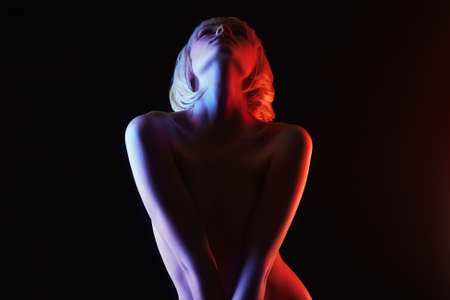 Nude Woman, Colorful bright lights posing in studio. Rainbow Naked silhouette of Blond Girl
