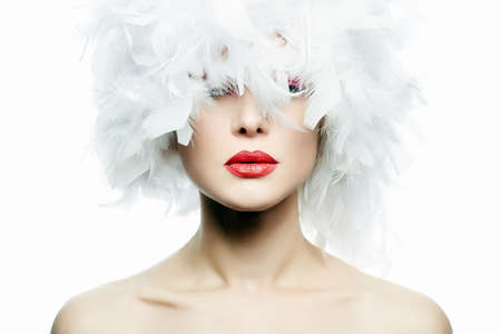 Beautiful Girl in white feathers. young Sexy Woman with red lips on pretty Face in beautiful feather Hat, closeup. Beauty Make-up Archivio Fotografico