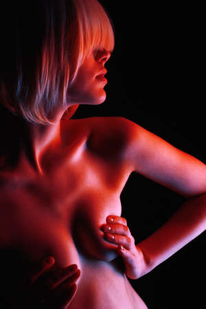 Beautiful Nude Woman in Red lights posing in studio. Naked Blond Girl with bob hairstyle Standard-Bild