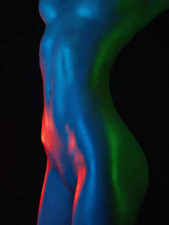 Rainbow Nude woman silhouette, woman in colorful bright lights posing in studio. Art design, colorful Naked girl Over black background