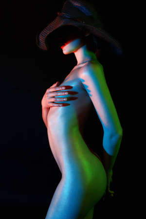 Nude Woman in Hat, Colorful bright lights. Different color sparkling shiny Naked body of Girl