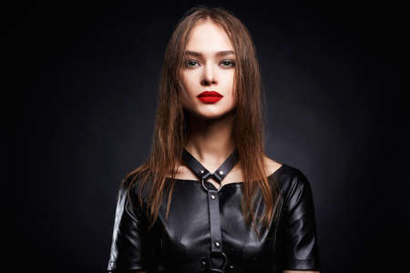 sexy Beautiful young woman in leather. beauty make-up girl, red lips, swordbelt 스톡 콘텐츠