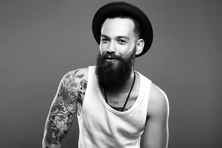 fashion black and white Portrait of young bearded Man in Hat and Tattoo. Smiling Hipster boy. handsome man in hat
