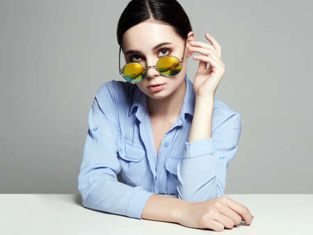 beautiful young woman in glasses sits at table. Studying girl. Yellow Sunglasses