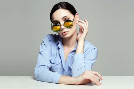 beautiful young woman in glasses sits at table. Studying girl portrait. Yellow Sunglasses