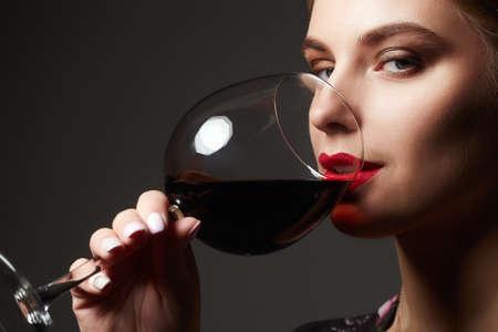 Beautiful happy woman drinking wine. beauty red lips make-up girl with wineglass 版權商用圖片