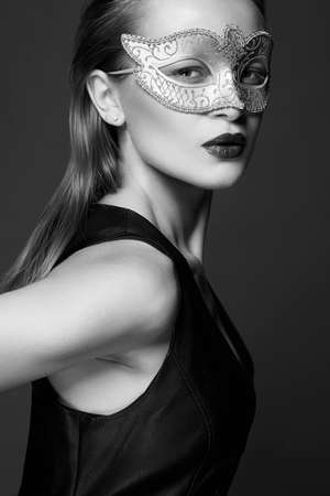 beautiful young woman in Mask. Beauty girl in Carnival Mask and leather dress. Masquerade Stock Photo