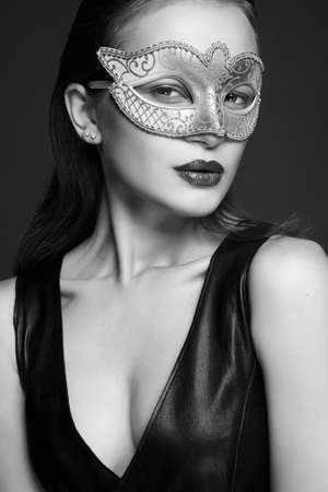 beautiful young woman in Mask. Beauty girl in Carnival Mask and sexual leather dress. Masquerade