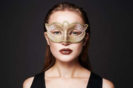 beautiful woman in golden mask. Beauty model girl in Mask