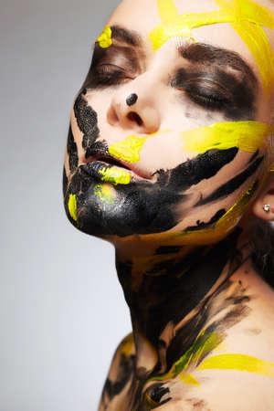 Young woman in paint beautiful face and Body. Color close-up portrait of Girl in Paint