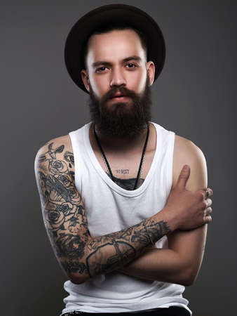 Handsome Tattooed Bearded Man in Hat. Brutal hipster boy with tattoo