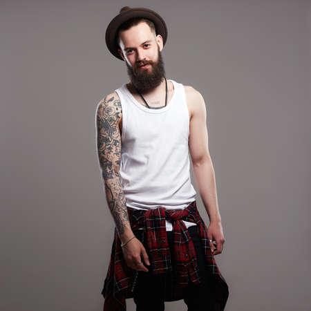 Mode Portrait des jungen bärtigen Mannes. Lächelnder Hippie-Junge. gut aussehender Mann mit Hut. Brutaler bärtiger Junge mit Tattoo