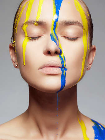 Young woman in Yellow and blue paint. liquid paint flowing over a beautiful face and Body. Color portrait of Girl in Paint