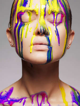 Girl in Multicolor Paint. liquid paint flowing over a beautiful face and Body. Colors of woman