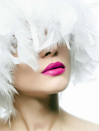 Portrait of Beautiful Girl in white feathers. young sexy woman with pink lips, beautiful feather hat. Beauty make-up