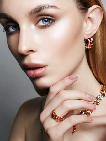 Gold jewelry on beautiful girl. young blonde woman with make-up and jewels accessories. Beauty Fashion Portrait 版權商用圖片