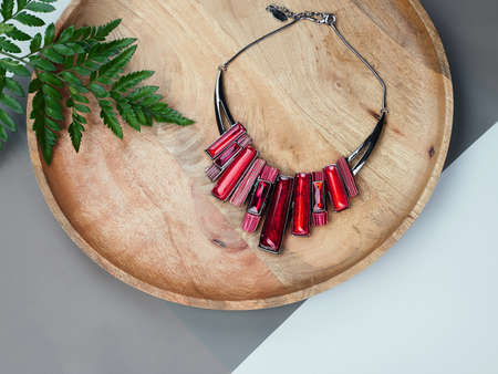 Woman's Jewelry. Ruby necklace on wooden desk. Beautiful accessories background Archivio Fotografico