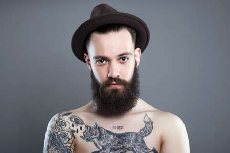 Handsome Bearded Man in Hat. Hipster boy with tattoo body Stockfoto