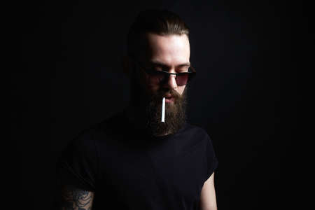 Hipster boy with cigarette. handsome Brutal bearded smoking man in sunglasses