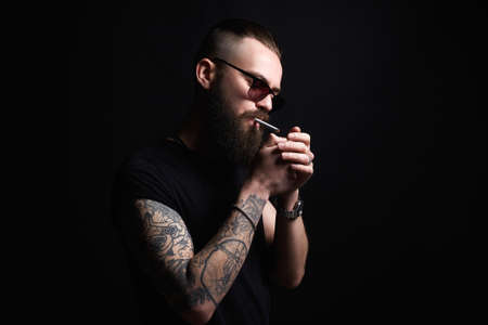 man lights a cigarette. handsome Brutal bearded smoking man in sunglasses. Hipster tattoed boy