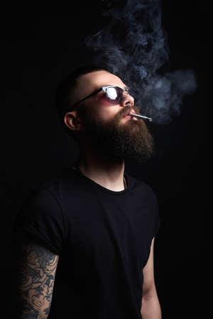 Brutal bearded smoking man in sunglasses. Hipster, tattoed boy with cigarette